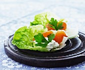Smoked salmon with cream cheese on a bed of lettuce