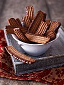 Chocolate biscuits with chocolate glaze in a white porcelain bowl