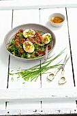 Green bean salad with rocket, bacon, egg, chives and an onion dressing