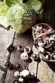 Field mushrooms on a wooden table and in a wooden basket next to organic savoy cabbage