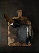 A vase, a plate and cutlery on a rustic wooden board on a dark surface