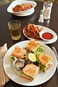 Vegan club sandwich with seitan tofu and sweet potato fries