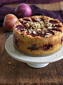A whole gluten-free plum cake with almonds and crumbles on a round plate