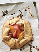 A peach and plum tart on a baking tray lined with paper