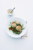 Fish cakes on a bed of tomato and rocket salad