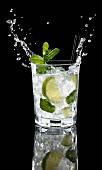 A splashing glass of vodka lemon against a black background