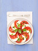 Tomatoes with mozzarella, capers and basil