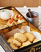 Parmesan biscuits with rosemary in a biscuit tin