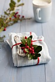 A napkin and an old-fashioned spoon decorated with holly