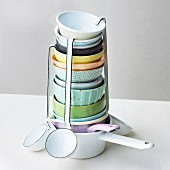 A stack of soup bowls, ladles and saucepans