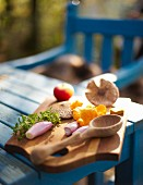 Mushrooms, shallots, herbs and an apple on a chopping board on a garden table