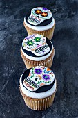 Three cupcakes decorated with skulls for Halloween