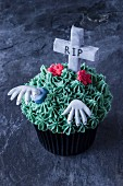 A gruesome cupcake for Halloween decorated with a grave