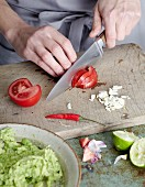 Guacamole being made: tomatoes, chilli and garlic being chopped