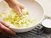 Grated white cabbage being mixed with salt