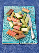 Sliced rhubarb on pastel-blue ceramic tiles
