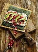 Sushi with pomegranate seeds, avocado and salmon