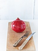 A pomegranate on a wooden board