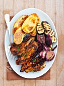 Grilled pork ribs with courgette, onion and baked potatoes