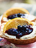 A wholemeal roll with blueberry and orange marmalade garnished with orange wedges