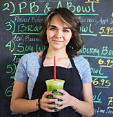 A young woman in a cafe holding a green smoothie in a plastic cup