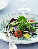 A mixed salad with green asparagus, lettuce, almonds and tomatoes