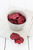 Beetroot chips in a bowl and on a cloth