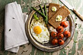 Fried egg with steamed tomatoes, asparagus and rye bread
