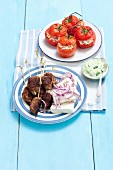 Tomatoes filled with rice served with koftas with feta and onions
