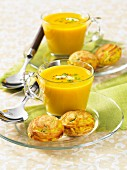 Two glasses of curry soup with savoury pastries