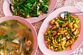 Thai dishes: chicken with cashew nuts, tom yam soup and vegetables