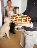 A man serving a pecan pie on a cake stand for Thanksgiving