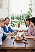 Two couples sitting at a dinning table together
