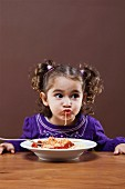 A little girl eating spaghetti sucking a strand into her mouth