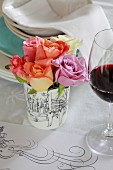 Table centrepiece of roses next to glass of red wine