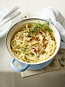Spaghetti with a cheese sauce, pine nuts and thyme