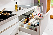 A white kitchen counter with an open drawer revealing spices and bottles