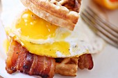 A savoury waffle sandwich for breakfast with bacon and fried egg