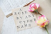 Two roses and a piece of paper with text stamped on it in front of old letters