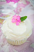 A lemon cupcake with buttercream and decorated with a flower