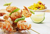 Crispy fried crayfish skewers with lime and grated coconut