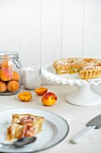 A sliced apricots pie with slivered almonds, one slice on a plate