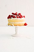 A birthday cream cake with raspberries