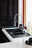 An anthracite coloured sink with a pull-down sprayer mixer tap set into a white work surface with a shiny black cupboard in the background
