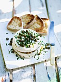 Goats cheese filled with tapenade and topped with capers and chives