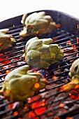 Halved artichokes on charcoal grill