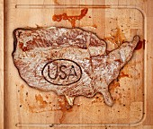 A beef steak with a USA stamp on a chopping board