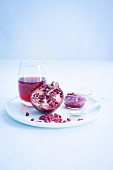 A glass of pomegranate juice, half a pomegranate and pomegranate seeds