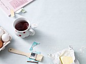 A cup of tea, a cook book and baking ingredients