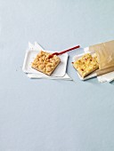 Two slices of tray bake cake on paper plates and in a paper bag